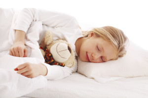 Cute little girl sleeping in her bed with teddy.